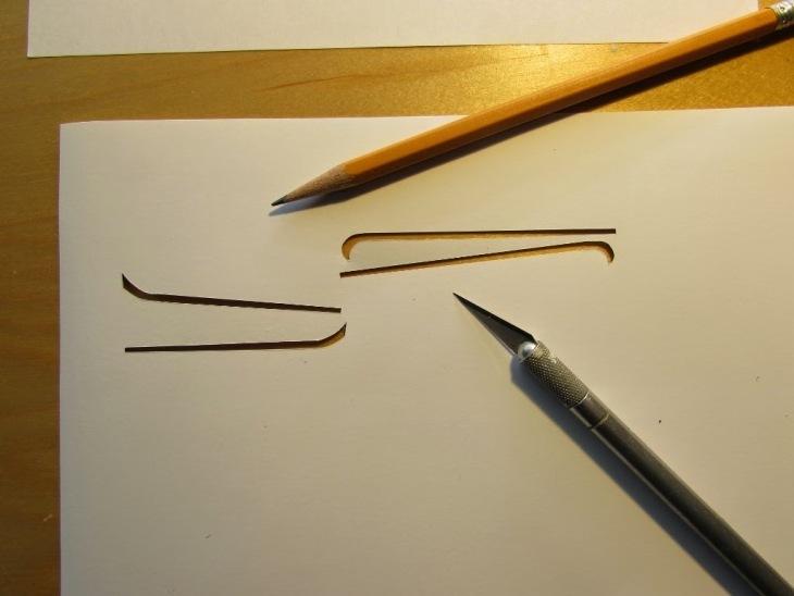 Le forme delle maschere vengono tagliate da un foglio di carta rigido